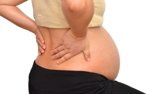 Pregnant woman bends over holding her back in pain