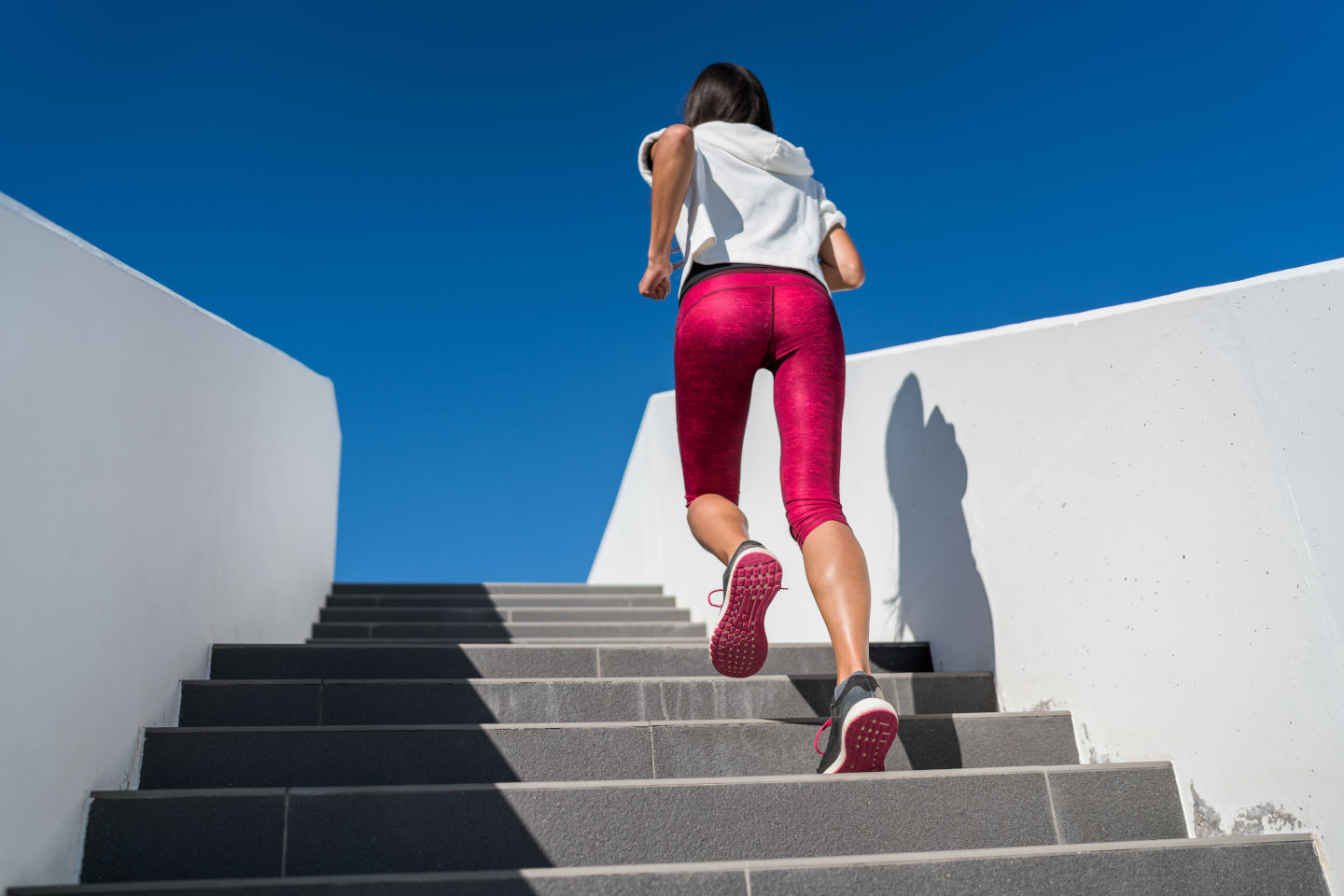 Stairs climbing running woman doing run up steps on staircase. Female runner athlete going up stairs in urban city doing cardio sport workout run outside during summer. Activewear leggings and shoes.