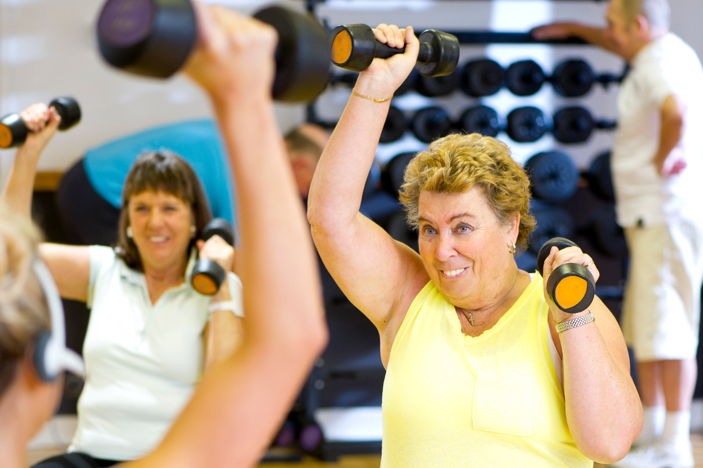 fun seniors workout. Two ladies doing shoulder press with dumbells.