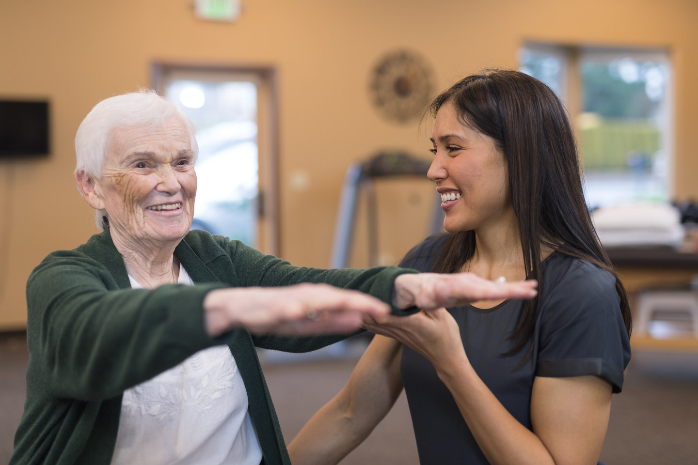 A female occupational therapist of Asian descent works with a cheerful senior female as she does exercises on an exercise ball. She is helping steady her as she holds her arms out.