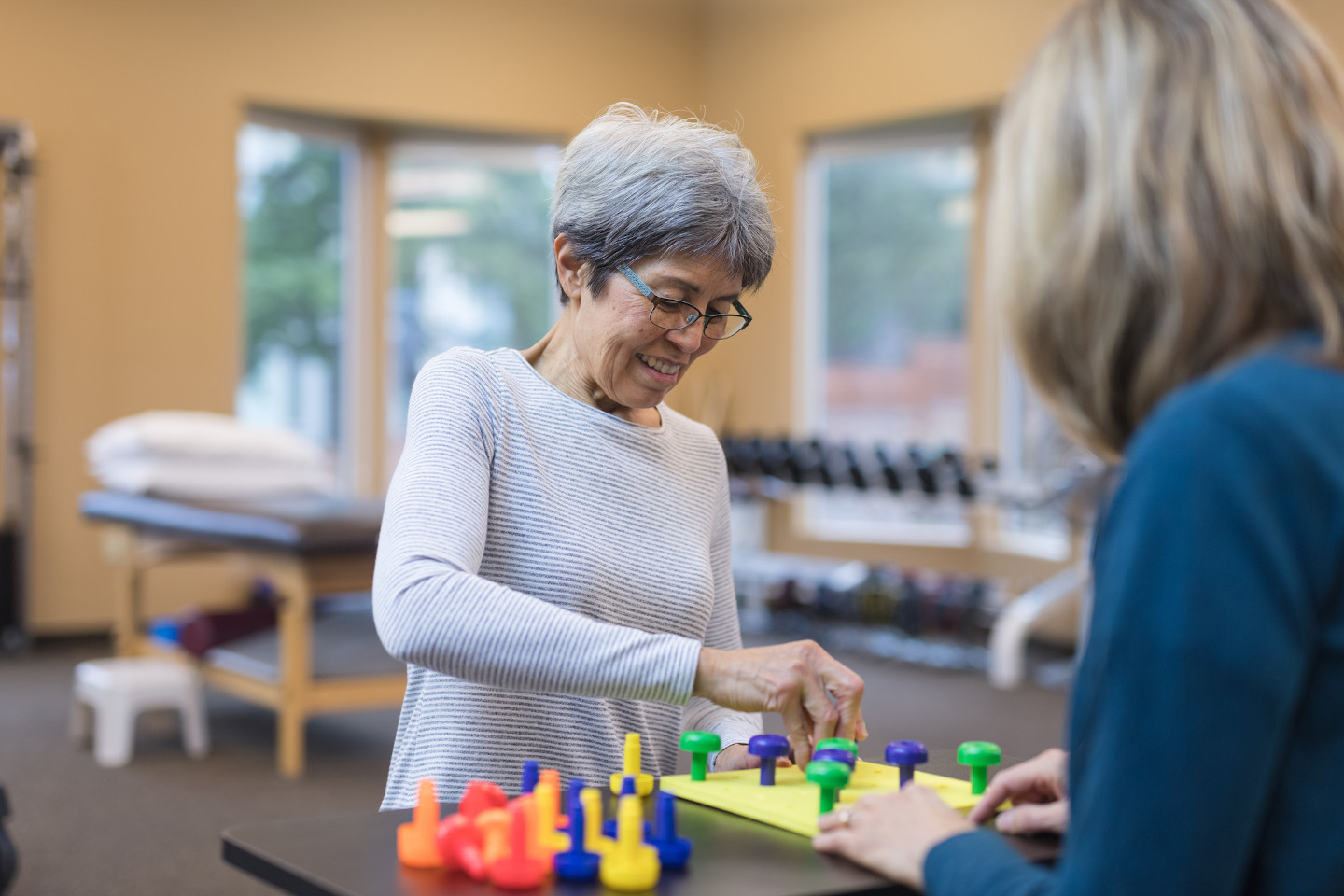An occupational therapist works with a senior Caucasian woman They are seated at a table and they are doing a fun exercise that involves putting pegs into a plastic board.